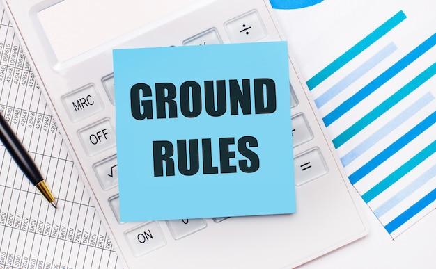 На рабочем столе белый калькулятор с синей наклейкой с текстом правила земли, ручкой и синими отчетами. бизнес-концепция