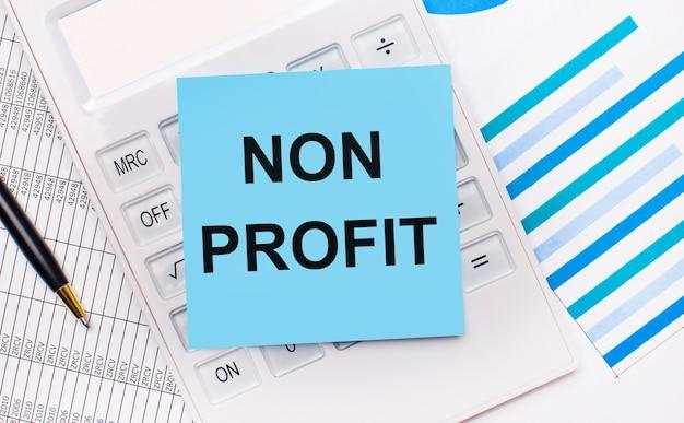 На рабочем столе белый калькулятор с синей наклейкой с текстом non profit, ручкой и синими отчетами. бизнес-концепция