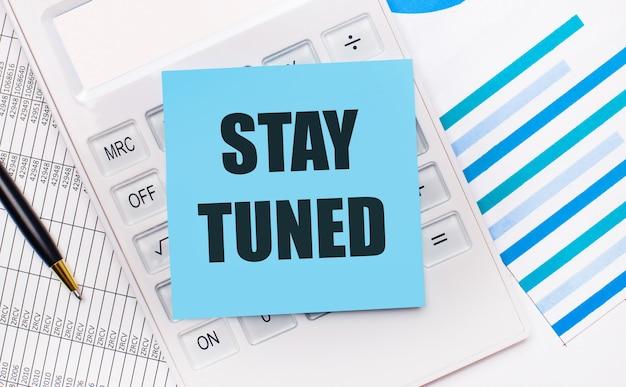 На рабочем столе белый калькулятор с синей наклейкой с текстом stay tuned, ручкой и синими отчетами. бизнес-концепция