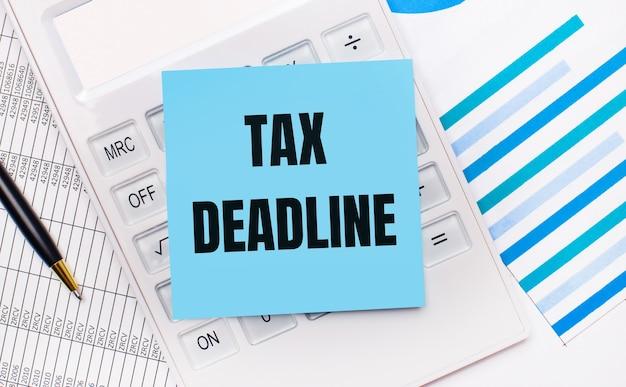 На рабочем столе белый калькулятор с синей наклейкой с текстом налоговый срок, ручка и синие отчеты. бизнес-концепция