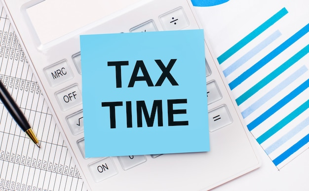 На рабочем столе белый калькулятор с синей наклейкой с текстом налоговое время, ручкой и синими отчетами. бизнес-концепция