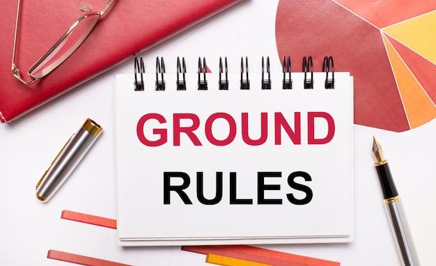 デスクトップには、ground rulesというテキストが書かれた白いノート、ペン、バーガンディと赤のテーブル、金枠のメガネがあります。ビジネスコンセプト。