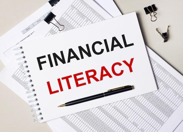 デスクトップには、ドキュメント、ペン、黒いペーパークリップ、およびfinancialliteracyというテキストのノートブックがあります。ビジネスコンセプト