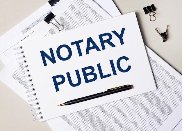 На рабочем столе документы, ручка, черные скрепки и записная книжка с текстом «нотариус». бизнес-концепция