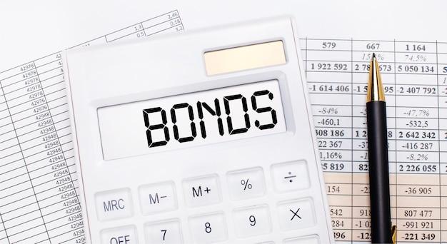 На рабочем столе есть отчеты, белый калькулятор с текстом bonds на табло и ручка. бизнес-концепция.
