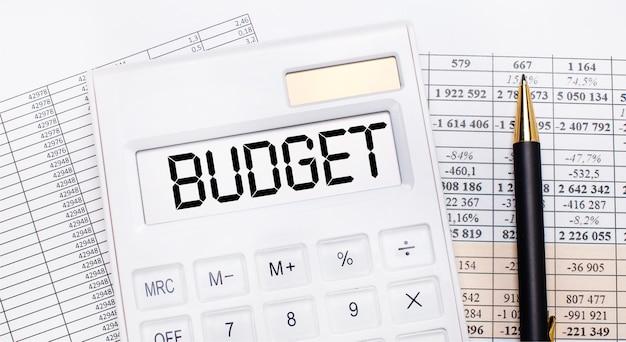 На рабочем столе отчеты, белый калькулятор с текстом бюджет на табло и ручка. бизнес-концепция.