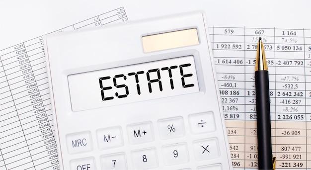 На рабочем столе отчеты, белый калькулятор с надписью estate на табло и ручка. бизнес-концепция.