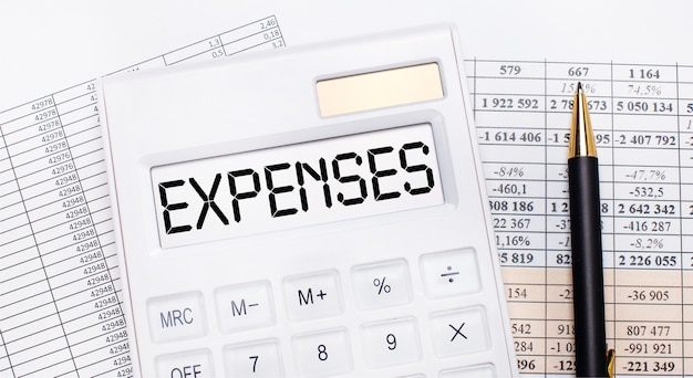 デスクトップには、レポート、スコアボードにexpensesというテキストが表示された白い電卓とペンがあります。ビジネスコンセプト。