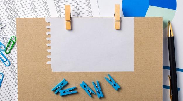 デスクトップには、レポート、青い洗濯バサミとチャート、ペン、ノートブック、テキストを挿入する場所のある白紙があります。テンプレート。ビジネスコンセプト