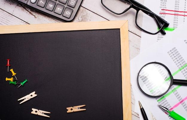 デスクトップには、電卓、レポート、メガネ、虫眼鏡、ペン、テキストを挿入する場所のあるボードがあります。レンプレート。ビジネスコンセプト