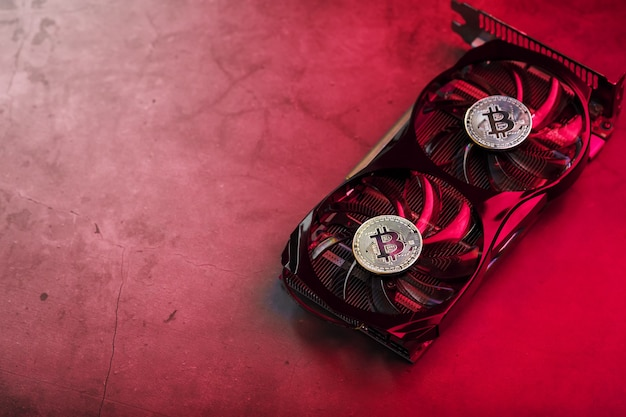 強力なビデオカードのファンには、赤いバックライト付きのビットコイン暗号通貨のコインが表示されます。暗号通貨のマイニングとマイニングの概念は暗号通貨ファームです。