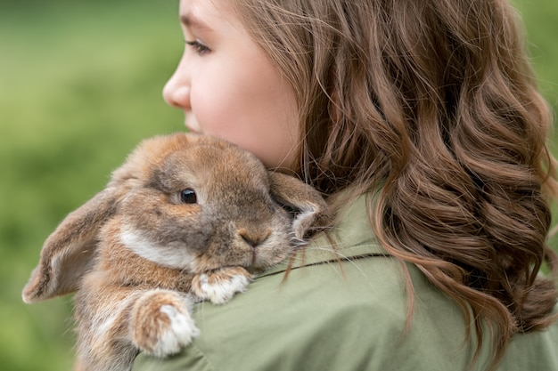 소녀의 어깨에 귀여운 생강 국내 토끼가 놓여 있습니다.