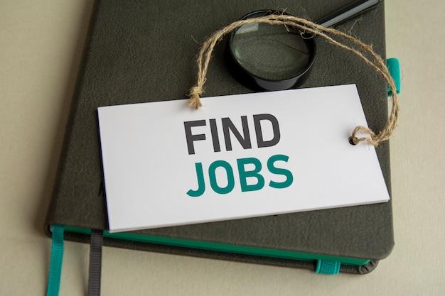На сером блокноте увеличительное стекло и белая бумажная карточка с надписью найди работу, выборочный фокус.