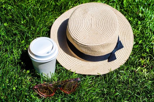 緑の芝生の上に麦わら帽子、コーヒー、サングラス、木製の文字があります。夏という言葉。夏の背景。休暇、週末