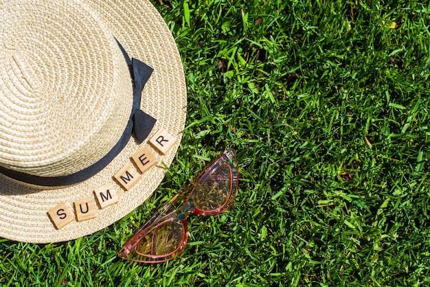 緑の芝生の上に麦わら帽子、サングラス、木製の文字。夏という言葉。夏の背景。休暇、週末。