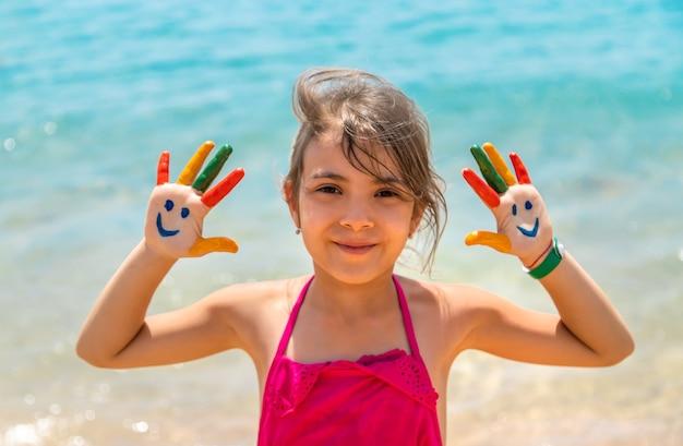 子供の手に、海に絵の具で笑顔 Premium写真