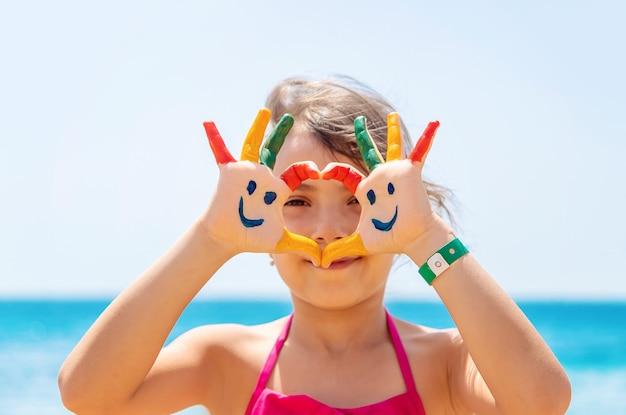 子供の手に、海に絵の具で笑顔