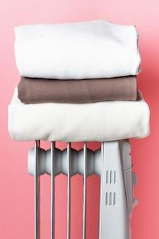 На обогревателе у розовой стены - стопка одежды.