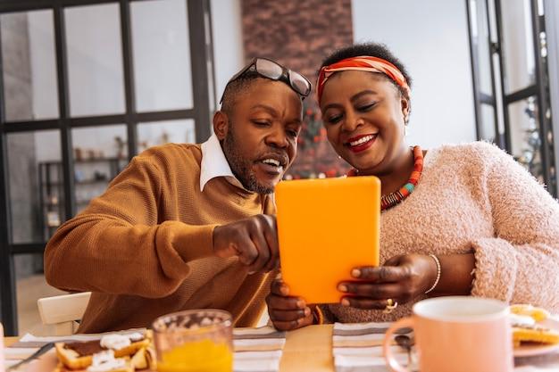 인터넷에서. 인터넷을 서핑하는 동안 최신 태블릿을 사용하는 즐거운 긍정적 인 커플