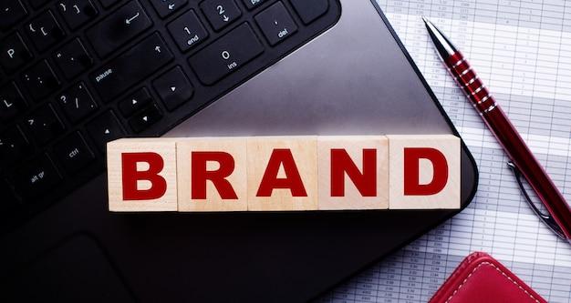 На клавиатуре рядом с бордовой шариковой ручкой деревянные кубики с надписью brand.