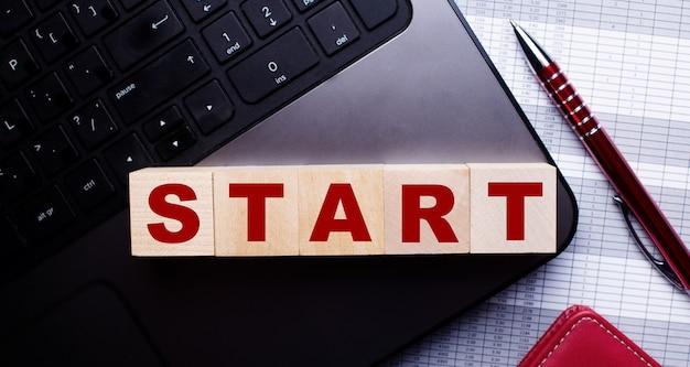 На клавиатуре рядом с шариковой ручкой бордового цвета деревянные кубики с надписью start.