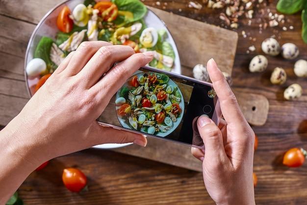 木の板の台所のテーブルに自家製サラダのプレート。電話で女性の手がサラダの写真を作ります。