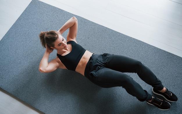 매트 위에. 체육관 바닥에서 복근을한다. 아름 다운 여성 피트 니스 여자입니다.