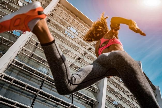 移動して。マラソンに参加中の若い女性ランナーのローアングル