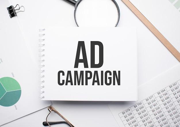 テキスト広告キャンペーン、拡大鏡、チャート、メガネを書くためのメモ帳。