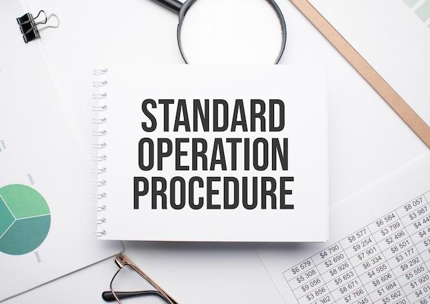 На блокноте для написания текста стандартная процедура работы, лупа, диаграммы и очки.