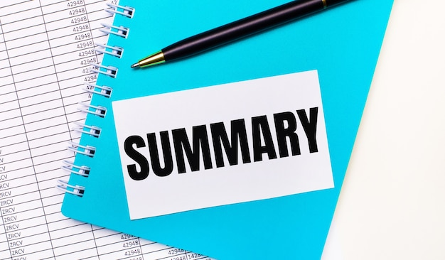 オフィスの机には、レポート、青いメモ帳、黒いペン、そして「summary」というテキストが書かれた白いカードがあります。スタイリッシュな職場。ビジネスコンセプト