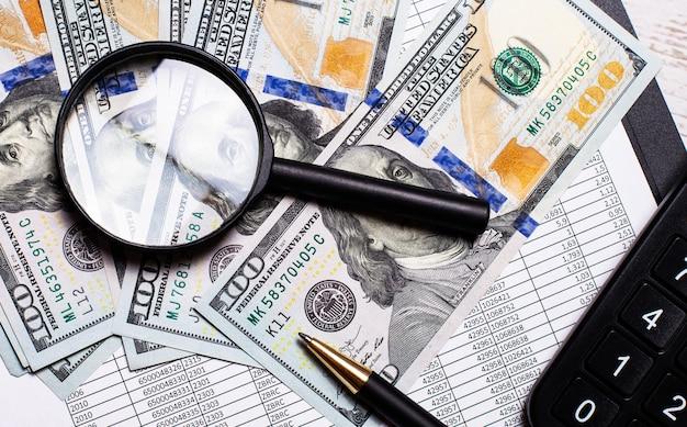 На офисном столе доллары, увеличительное стекло и ручка. бизнес-концепция. на рабочем месте крупным планом