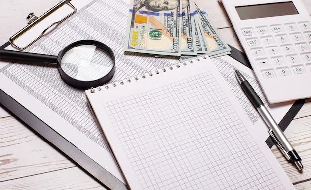 На офисном столе отчеты, очки в черной оправе, доллары, калькулятор, увеличительное стекло и блокнот с ручкой. бизнес-концепция. на рабочем месте крупным планом