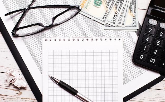 На офисном столе отчеты, очки в черной оправе, доллары, калькулятор и блокнот с ручкой. бизнес-концепция. на рабочем месте крупным планом