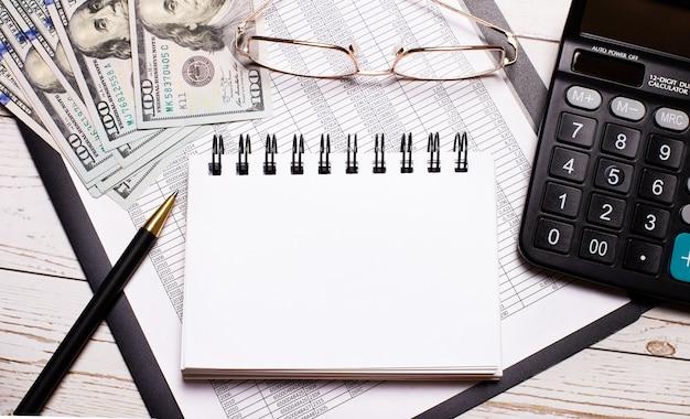 オフィスのテーブルには、電卓、テキストを挿入する場所のあるノート、ペン、眼鏡、ドルがあります。スタイリッシュな職場。ビジネスコンセプト