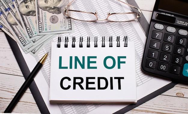 オフィスのテーブルには、電卓、line of creditのテキストが書かれたノート、ペン、メガネ、ドルがあります。スタイリッシュな職場。ビジネスコンセプト