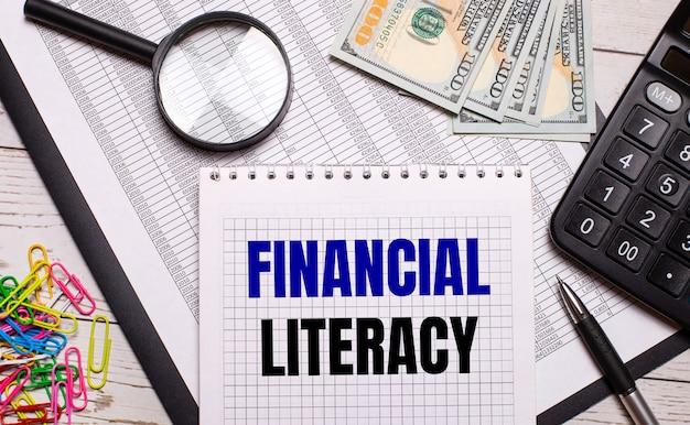 На офисном столе тетрадь с текстом «финансовая грамотность», ручка, калькулятор, доллары, разноцветные скрепки и лупа. стильное рабочее место. бизнес-концепция
