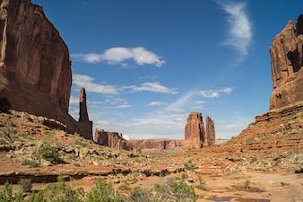 On the Park Avenue trail in Arches National park against blue sky.