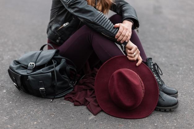포장 도로에는 가죽 배낭이 달린 세련된 부츠에 보라색 바지에 검은 세련된 재킷을 입은 젊은 여성이 앉습니다.
