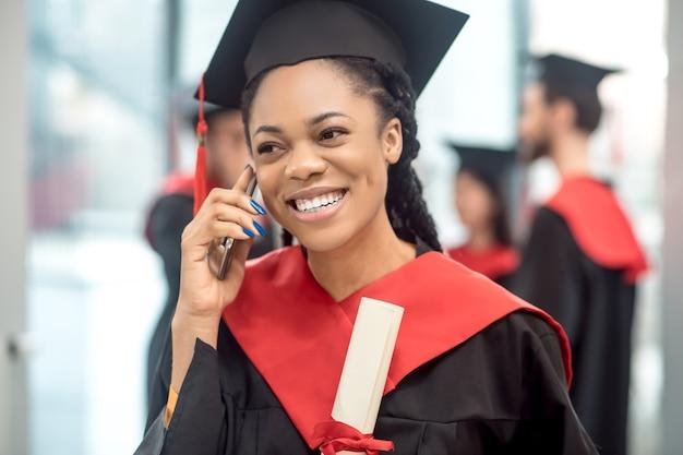 電話で。電話で話している浅黒い肌の卒業生の笑顔