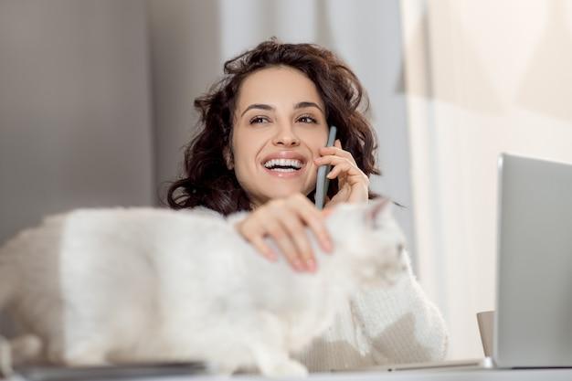電話で。電話で話し、幸せそうに見える若い女性の笑顔
