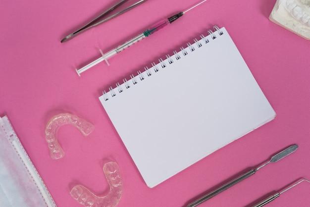 분홍색 표면에는 치과 기구, 흰색 공책 및 치아용 접시가 있습니다.
