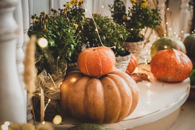 ベランダにはオレンジ色のカボチャと花があります。ハロウィーンの休日。敷居は野菜の収穫で飾られています。