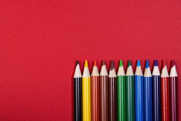 赤い表面には木の色の学校の鉛筆があります。上面図。概要。