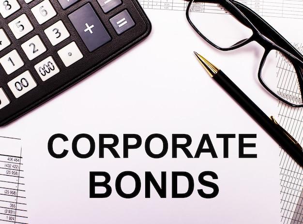 На отчетах калькулятор, очки, ручка и блокнот с надписью corporate bonds.