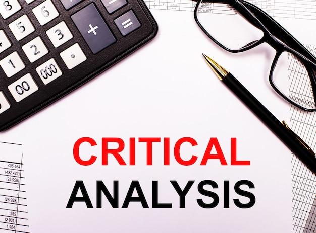 На отчетах калькулятор, очки, ручка и блокнот с надписью критический анализ.