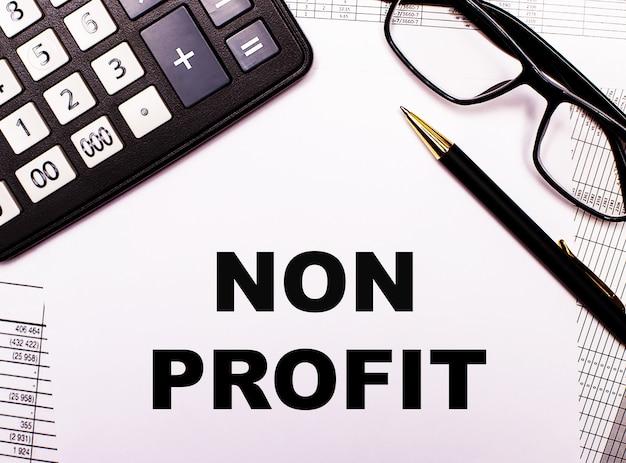 На отчетах калькулятор, очки, ручка и блокнот с надписью non profit.