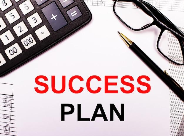 レポートには、電卓、メガネ、ペン、そしてsuccessplanと書かれたノートがあります。