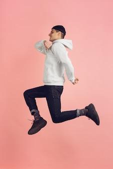 실행에. 분홍색 스튜디오 배경에 격리된 백인 청년의 현대적인 초상화. 높이뛰기에서 아름 다운 남성 모델입니다. 인간의 감정, 표정, 판매, 광고의 개념. 카피스페이스.