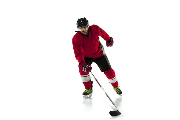 逃走中。アイス コートと白い背景にスティックを持つ男性のホッケー選手。スポーツマン着用の機器とヘルメットの練習。スポーツのコンセプト、健康的なライフスタイル、動き、動き、行動。